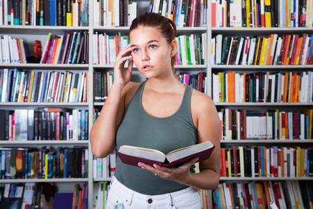 puzzled girl chooses a book in the library Stock Photo