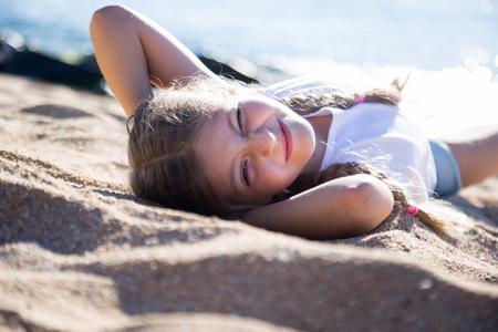 blond child girl lying on sandy beach of sea coast Foto de archivo