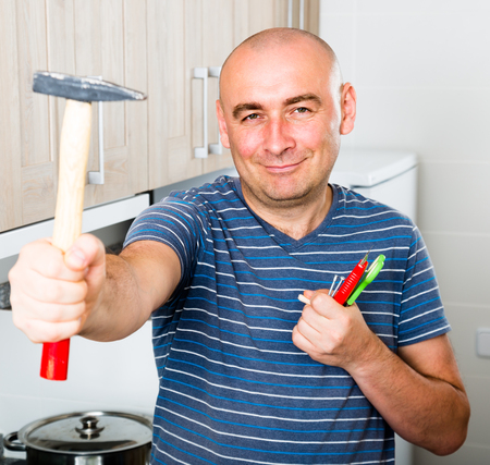 ordinary guy posing with a hammer in his hands