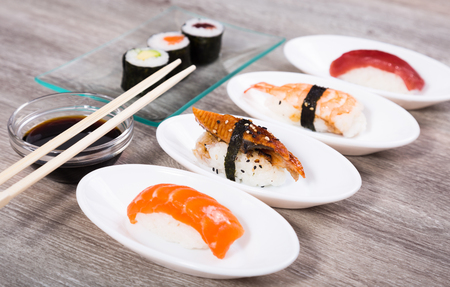 four kinds Nigirisushi on oval saucers and makizushi. focus on unagi