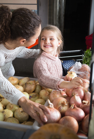 portret of young woman with beautiful smiling daughter choosing onions at store