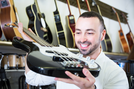 Positive male customer choosing electric guitar in music shop Reklamní fotografie