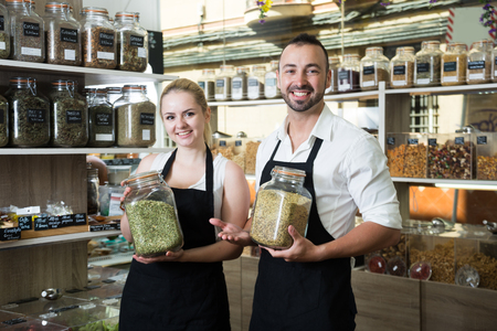 sellers posing with banks of dried herbs in store
