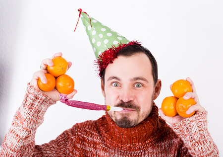 Portrait of Man on holiday in hat and whistle with tangerines Stock Photo