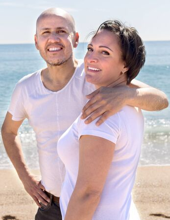 mature man and female cuddling near sea and smiling. focus on woman