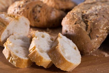 fresh slices of wheaten bread on wooden surface Standard-Bild