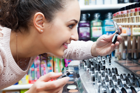 Positive brunette female customer selecting eye shadow in a store cosmetics