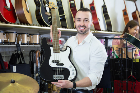 Positive male buyer choosing electric guitar in music store