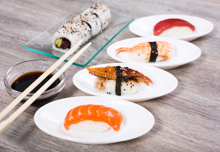 different kinds of japanese Nigirisushi on oval saucers and Uramaki