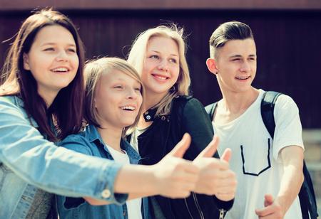 grupo de adolescentes muestran sus pulgares hacia arriba Foto de archivo