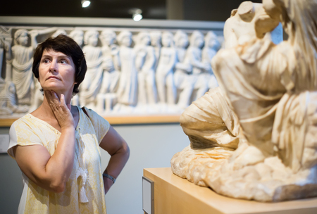 mature woman examines the exhibit in historical museum