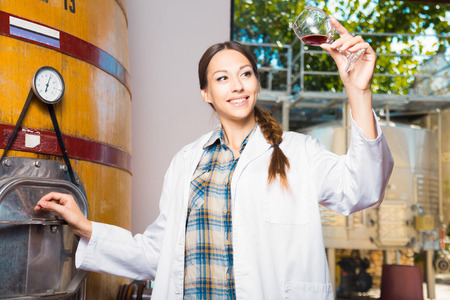 young female employee in white robe posing at winery