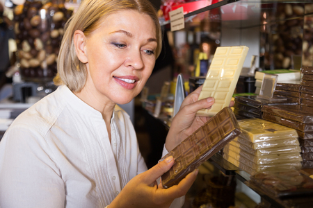 Happy female person buying dark and white chocolate in candy shop Фото со стока - 117430286