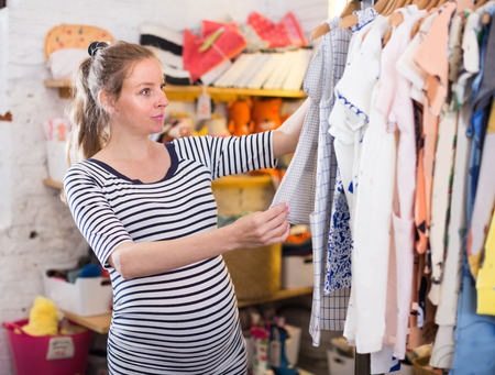 blonde expectant mother In striped tunic shopping Dress in clothing store for babies Banque d'images
