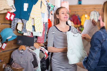 seller offers nice pregnant woman baby dress in clothing store Фото со стока - 117959356