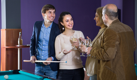 two adult couples of different generations talk in the billiard room Stockfoto