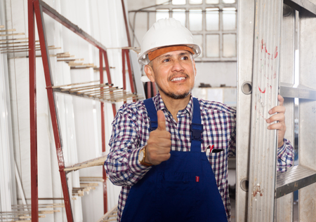 smiling Happy professional worker in uniform at modern industry plant Stock Photo