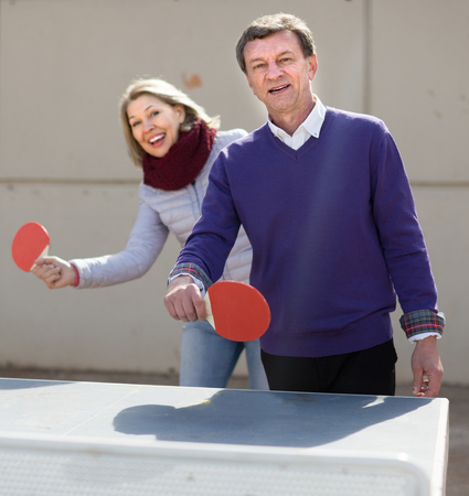Happy mature couple playing ping pong outdoors Reklamní fotografie