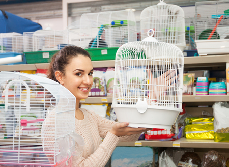 Average female buying cage for hamster in shop