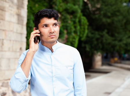 ordinary modern guy walks in city and communicates on smartphone