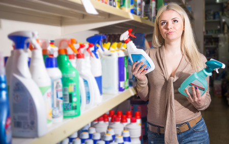 Young female customer buying detergents for laundry in shop