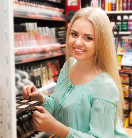 Woman selecting beauty treatment in makeup section Archivio Fotografico