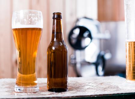 Flasche und Glas mit Bier auf Hintergrund von Fässern zur Gärung