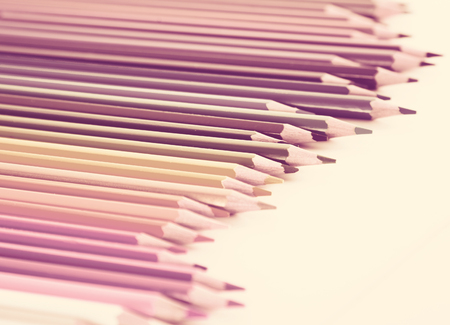 colored pencils lying in irregular row on white background
