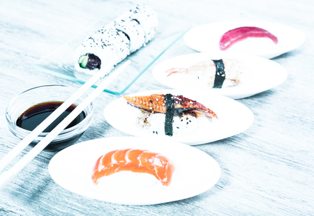 diferentes tipos de Nigirisushi japonés en platillos ovalados y Uramaki Foto de archivo