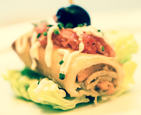 Exquisite pincho roll with olives on salad leaf
