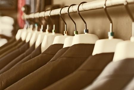 rij elegante jassen op hangers in herenkledingwinkel Stockfoto