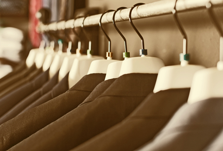 row of elegant jackets on hangers in men clothing store Stock Photo
