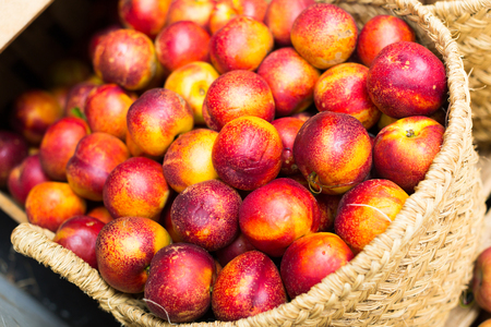 ripe aromatic nectarines in wicker baskets on counter