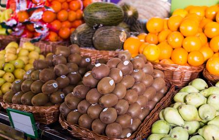many ripe kiwi in wicker baskets on counter market Archivio Fotografico