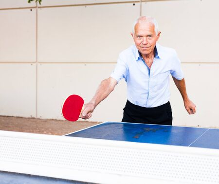 ordinary mature man playing table tennis outdoors