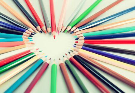 Buntstifte, die um das Herz auf weißem Hintergrund liegen