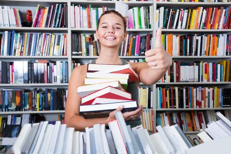 beautiful girl holding a stack of books in a bookstore and shows thump up