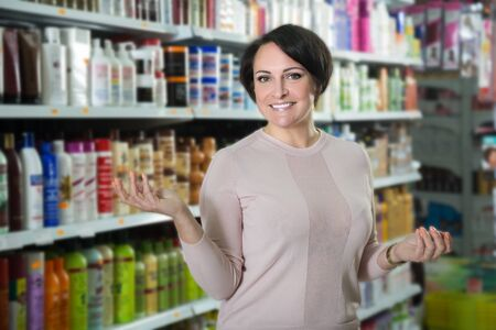 Positive woman buying hair care products in beauty salon and smiling