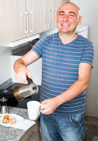 European gsmiling male pours coffee into cup of coffee pot