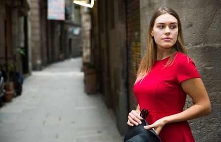beautiful young girl in red dress walks through the old European streets