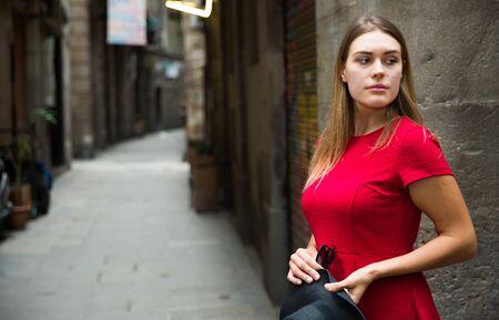 bella ragazza in abito rosso cammina per le vecchie strade europee