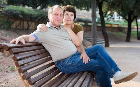 middleaged male and female posing on street bench