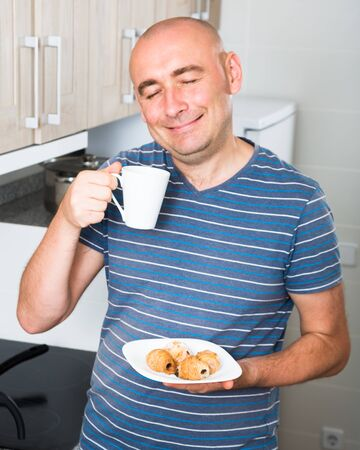 smiling guy with eyes closed drinking coffee and croissants in the morning