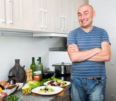 happy smiling man in the prime of life in kitchen prepared two salads