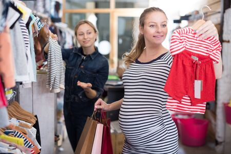 expectant mother in striped tunic chooses clothes for girl in boutique