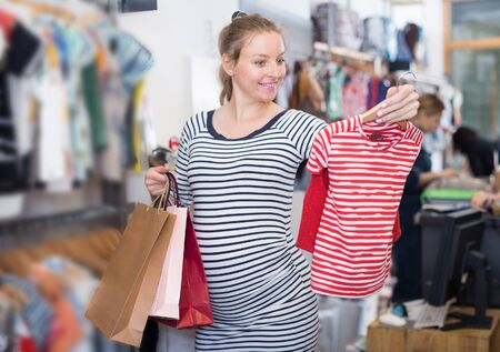 pregnant woman in striped tunic chooses striped shirt in clothing shop