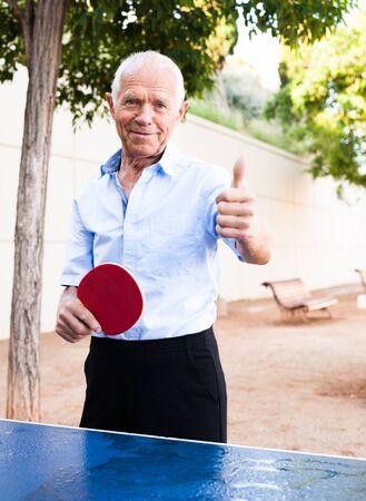 Hombre maduro feliz jugando tenis de mesa y mostrando el pulgar hacia arriba