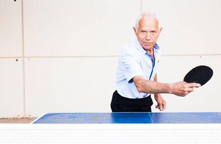 ordinary mature man playing ping pong outdoors