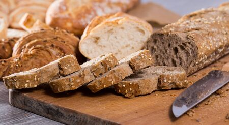 fresh slices of wheaten bread and knife on wooden surface Stock fotó