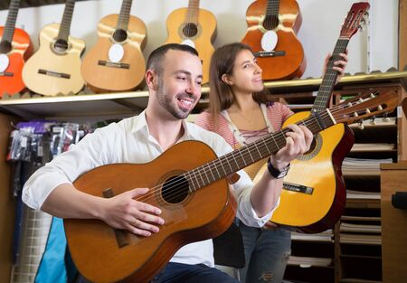 Positive young couple choosing new guitar in store and smiling Stock Photo
